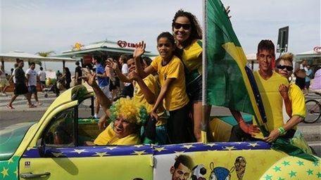 Soccer fans in Brazil's national team colors wave