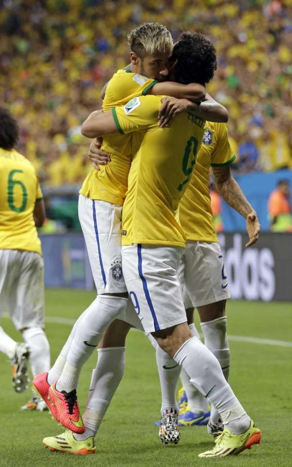 Brazil's Fred, right, hugs his teammate Neymar after