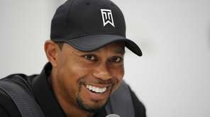 Tiger Woods smiles at a press conference at