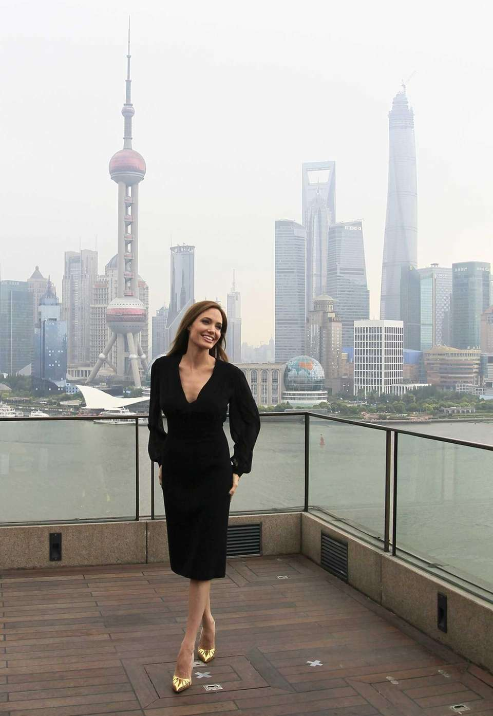 Angelina Jolie stands against a backdrop of the