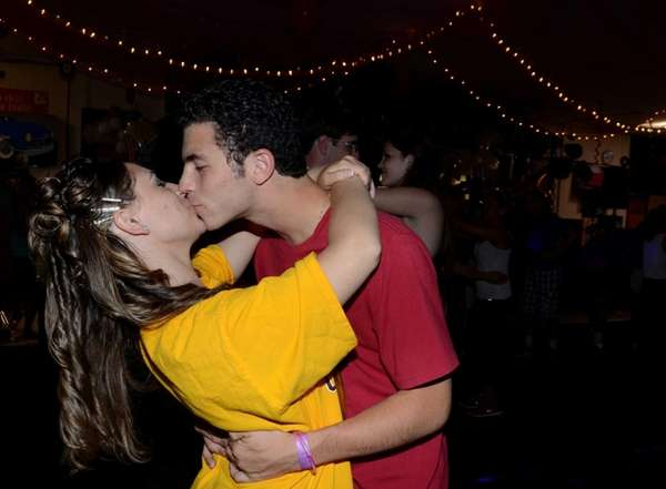 A couple shares a kiss while slow-dancing at