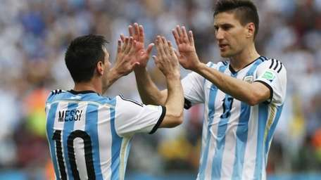 Argentina's Lionel Messi celebrates with teammate Federico Fernandez