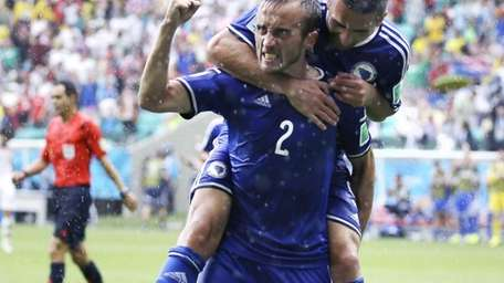 Bosnia's Avdija Vrsajevic celebrates with teammate Vedad Ibisevic