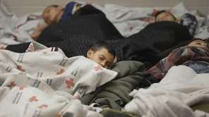 Children detainees sleep in a holding cell at
