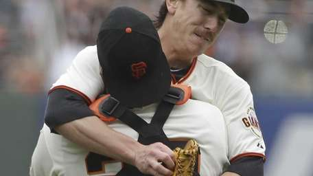 San Francisco Giants pitcher Tim Lincecum is embraced