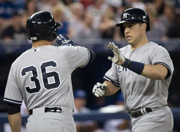 The Yankees' Mark Teixeira, right, celebrates his two-run