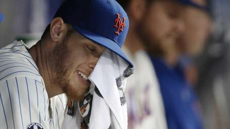 Mets starting pitcher Zack Wheeler wipes his face