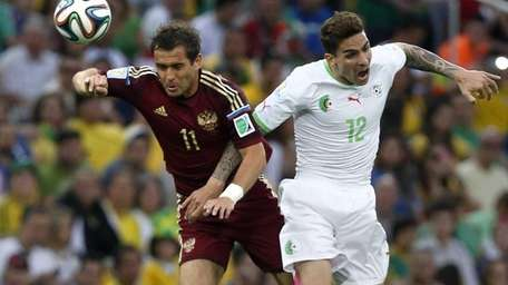 Russia's Alexander Kerzhakov and Algeria's Carl Medjani go