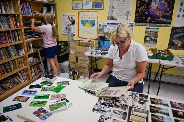 Volunteer archivist Pamela Hansen organizes old camp photos