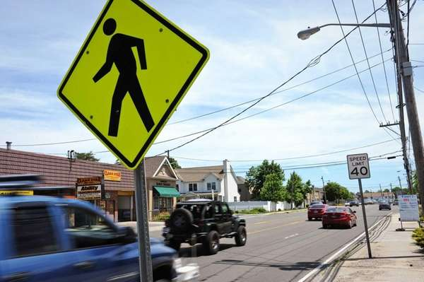 Vehicles drive down Montauk Highway near Strongs Avenue
