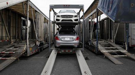 Mercedes-Benz sedans sit inside a car carrier before