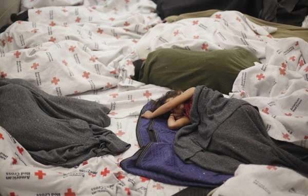 A detainees sleep in a holding cell at