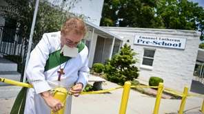 Deacon John Gallaer ties up crime scene tape