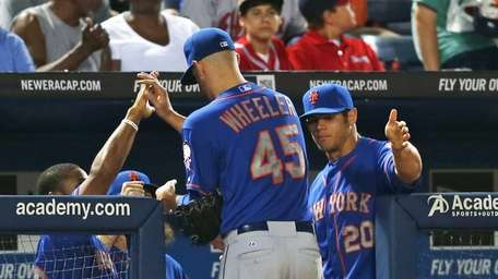 Mets starting pitcher Zack Wheeler is greeted at