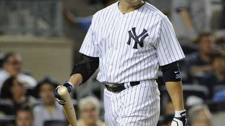 The Yankees' Carlos Beltran walks to the dugout