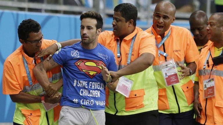 Stewards apprehend a man who ran onto the
