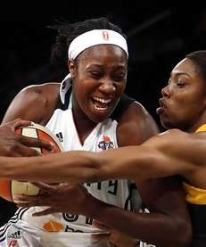 Liberty's Tina Charles, left, drives against Tulsa Shock's