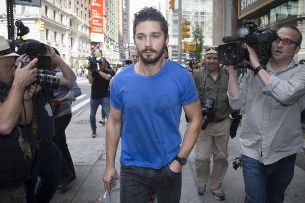 Shia LaBeouf walks through the media after leaving