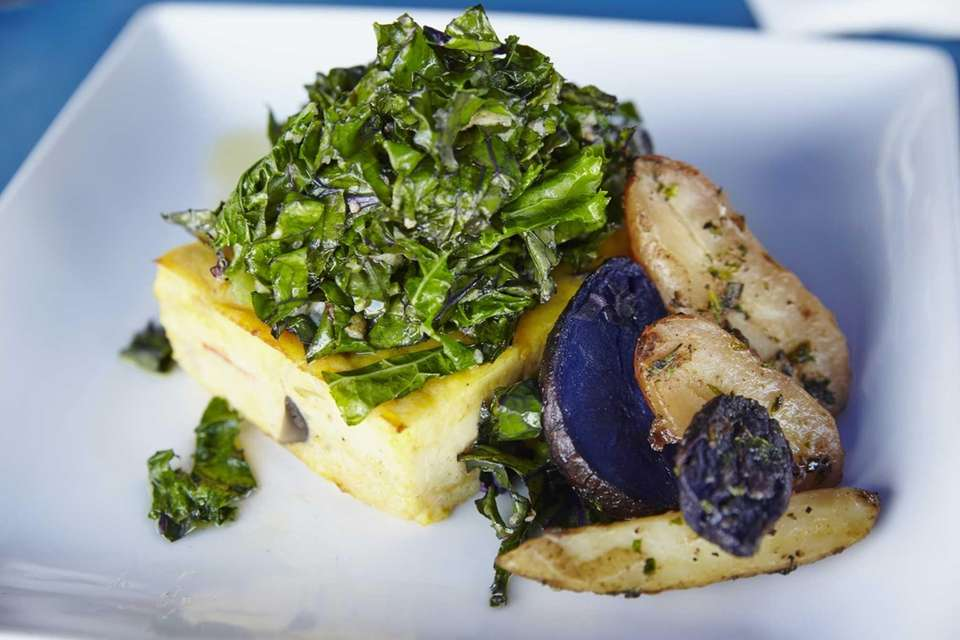 A mshroom cheese frittata, topped with wilted kale