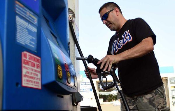 Lars Crosley, of East Northport, fuels a car