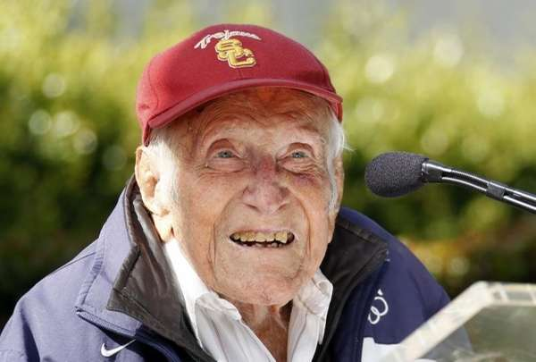 Louis Zamperini gestures during a news conference, in