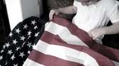 Little girl sewing an American flag.