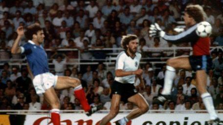 West German goalkeeper Harald Schumacher, right, jumps past