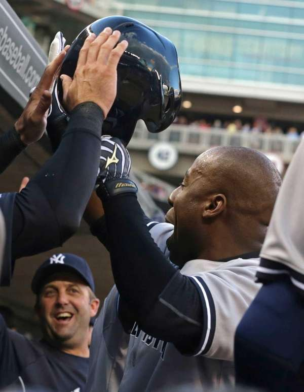 Yankees' Zelous Wheeler celebrates in the dugout after