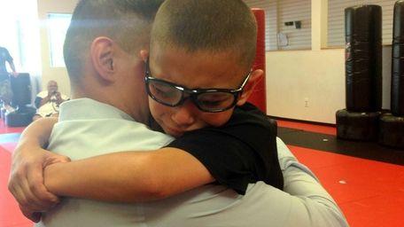 Mikey Ortiz, 9, wraps his arms around father