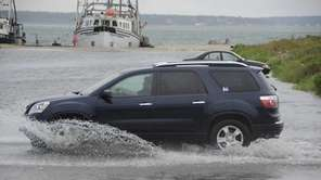 Cars plow through a flooded Dune Road in