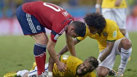Brazil's Neymar screams out after being fouled during