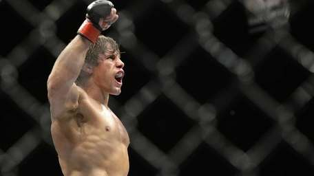 Urijah Faber celebrates after defeating Alex Caceres in