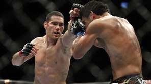 Chris Weidman, left, hits Lyoto Machida during their