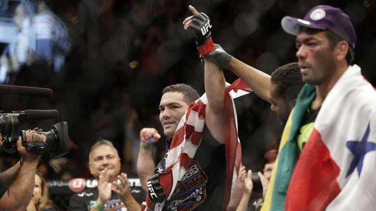 Chris Weidman celebrates after defeating Lyoto Machida, right,
