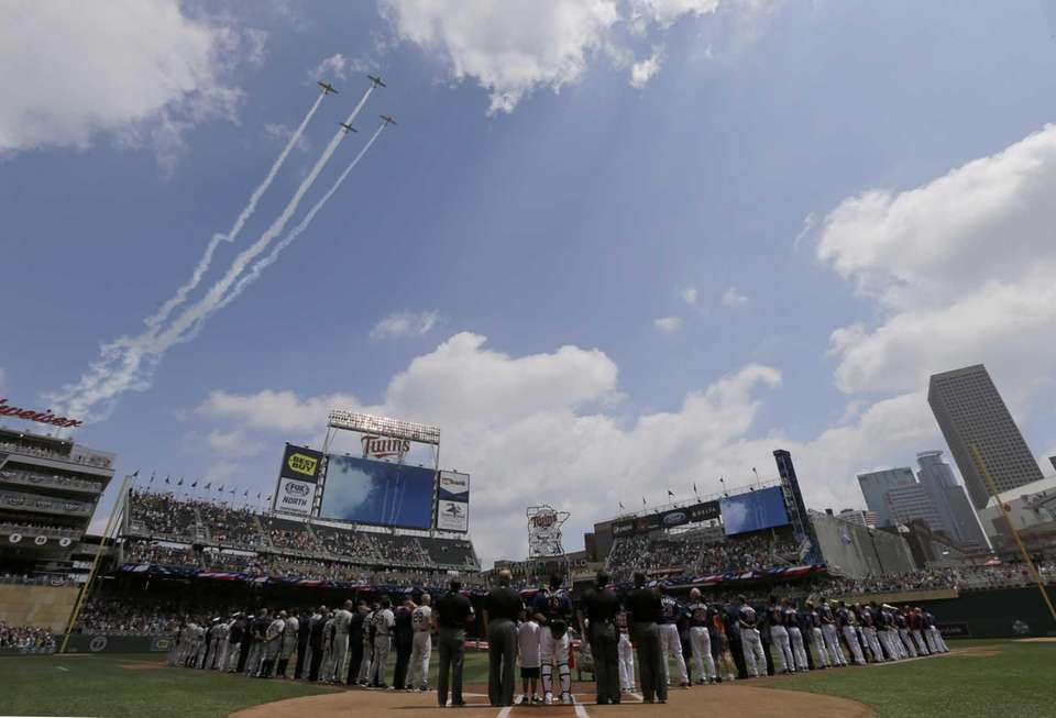 Military aircraft fly over Target Field during the