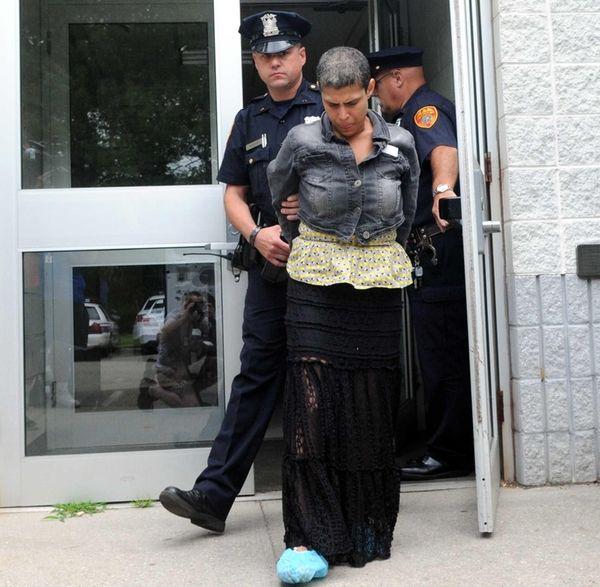 Police escort Elba Ayala, 43, of Shirley, out