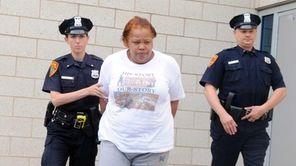 Police escort Kutima Glover, 33, of Huntington Station,