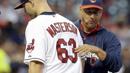 Cleveland Indians starting pitcher Justin Masterson, left, hands