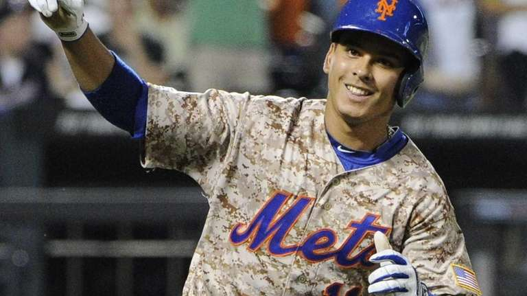 The Mets' Ruben Tejada reacts after hitting an