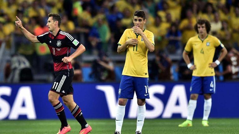 Germany's Miroslav Klose, left, celebrates after scoring his