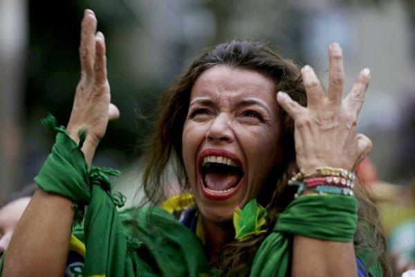 A Brazil soccer fan screams as Germany defeats