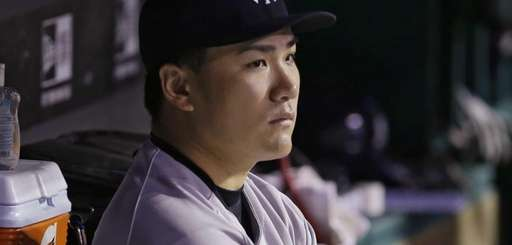 Yankees starting pitcher Masahiro Tanaka watches from the