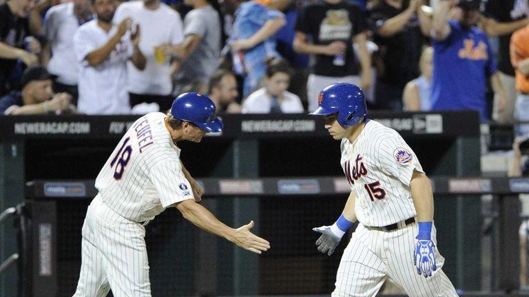 Mets third base coach Tim Teufel congratulates catcher