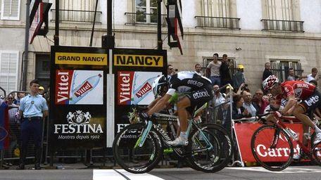 Italy's Matteo Trentin, front, crosses the finish line