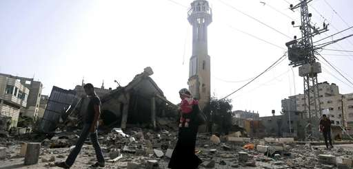 Palestinians walk past the ruins of the Al-Tawfeeq