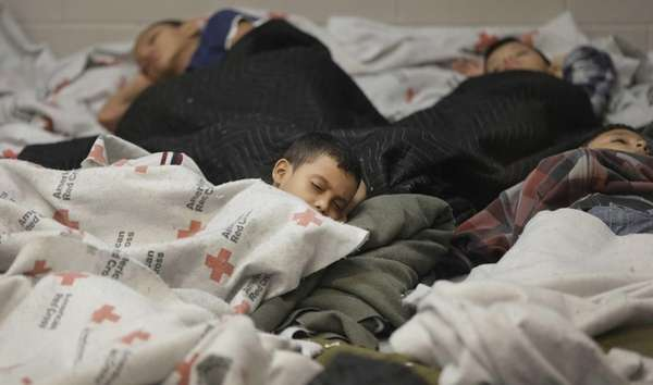 Detainees sleep in a holding cell at a