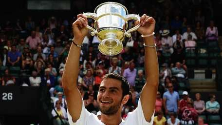 Noah Rubin celebrates with the winners trophy after