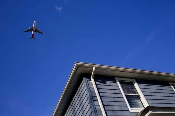 A large passenger jet passes over the home