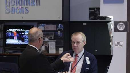 Stock traders work at the Goldman Sachs post