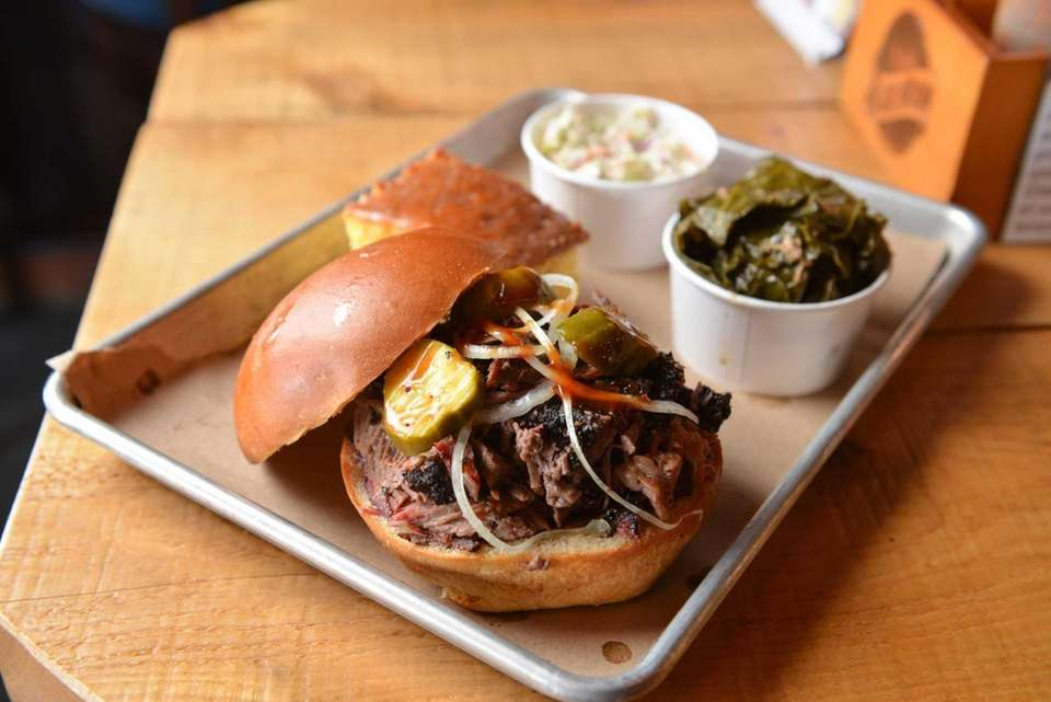 A chopped brisket sandwich is served with sides